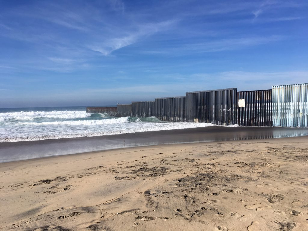 a wall juts out into the ocean dividing Tijuana, Mexico, and San Diego, California