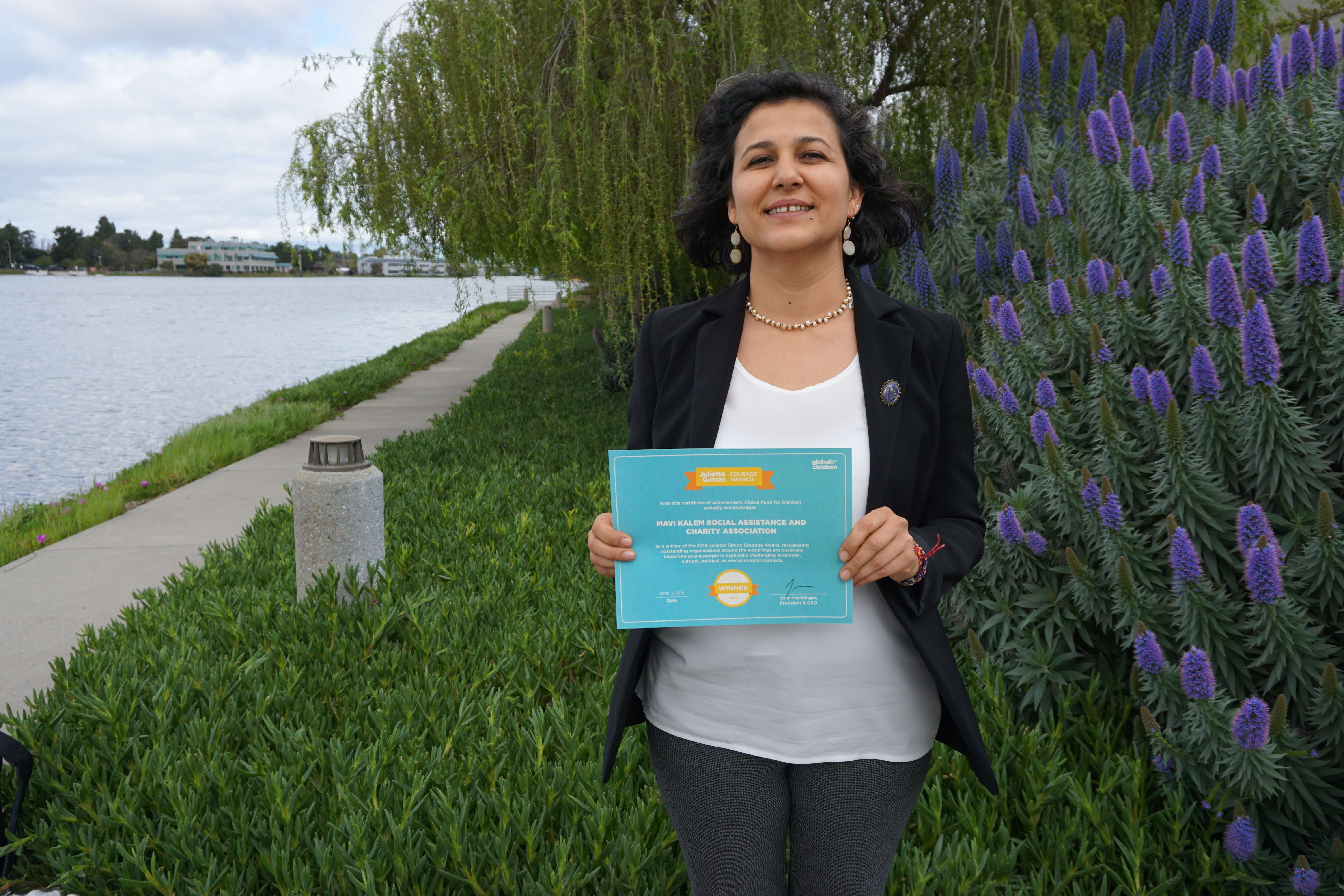 Gamze holding a Courage Award finalist certificate.