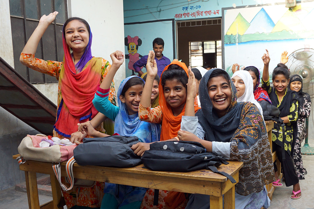 Bangladeshi girls raise their hands in a classroom at APON