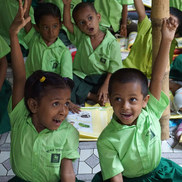 A group of children in green school uniforms raise their hands with excitement.