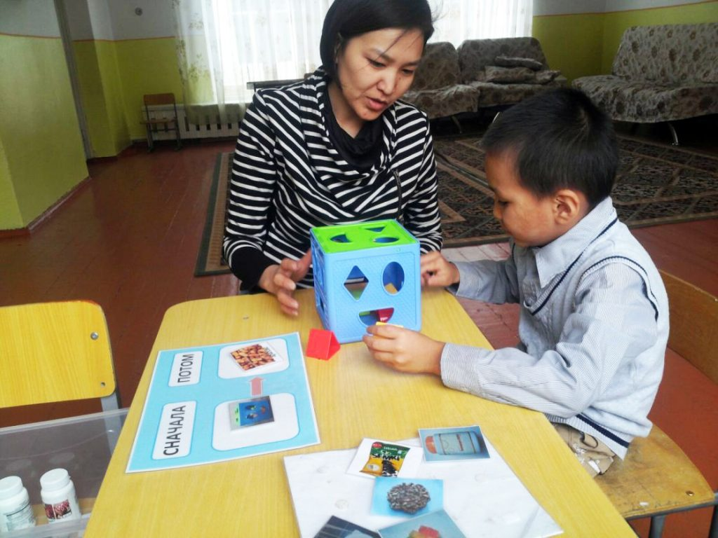 A therapist leads an educational therapy session with a child who has ASD