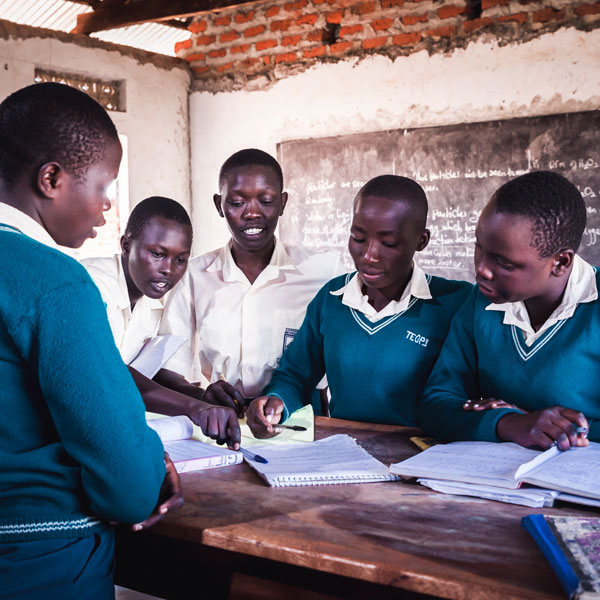 Youth look at and discuss at notes inside a school. © Giovanni Okot