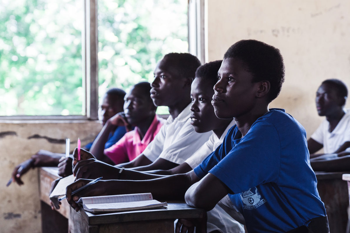 Youth sit at desks inside a school looking intently toward the front of the classroom. © Giovanni Okot