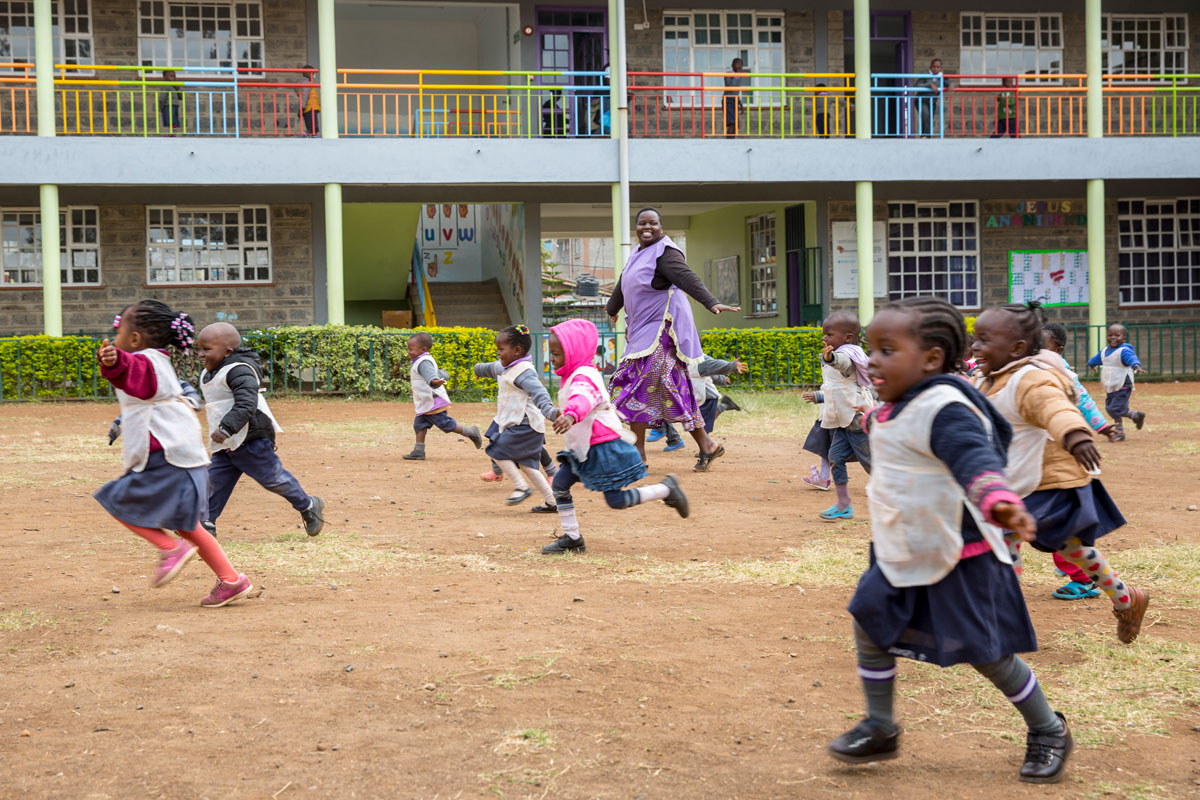 Smiling, primary-school-aged children run on a playground while their teacher watches. © Kevin Ouma