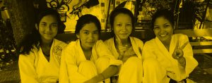 Four girls in karate uniforms sitting on a bench outside.