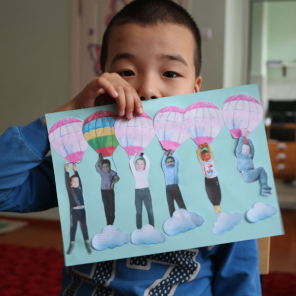 A boy holds up a piece of his artwork.