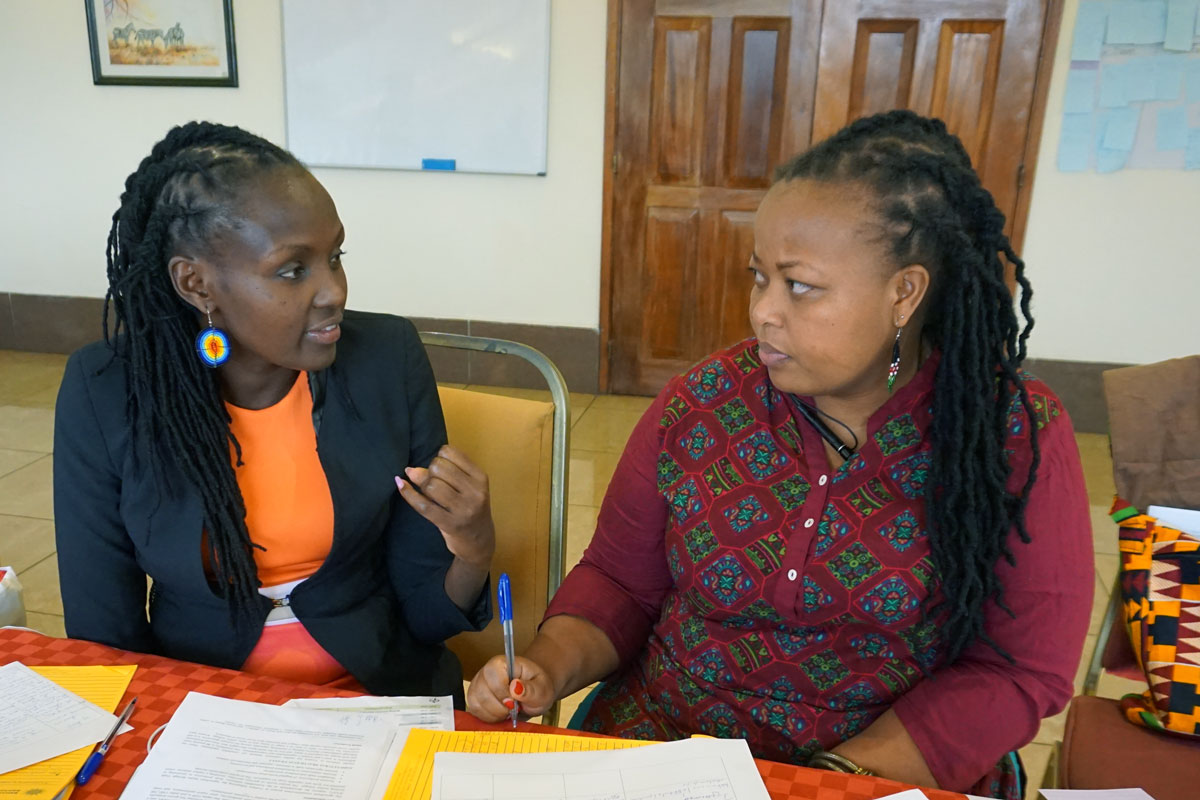 Two participants engage in discussion during the outcome harvesting workshop.