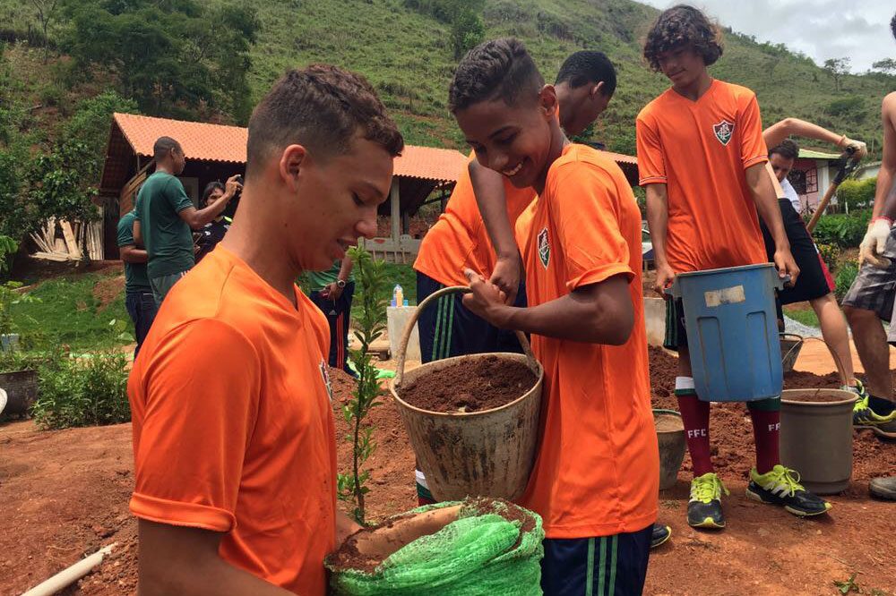 Four youth in orange shirts hold buckets with soil and plants outside. One smiles broadly while looking at the bucket.