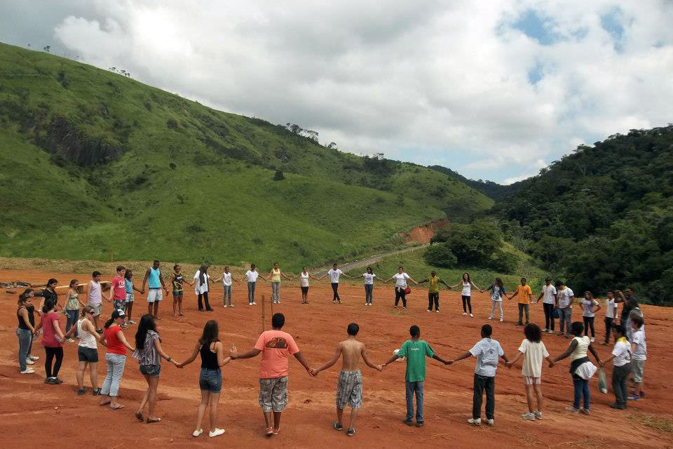 About 40 young people stand in a circle holding hands, beneath green mountains and a clouded sky.