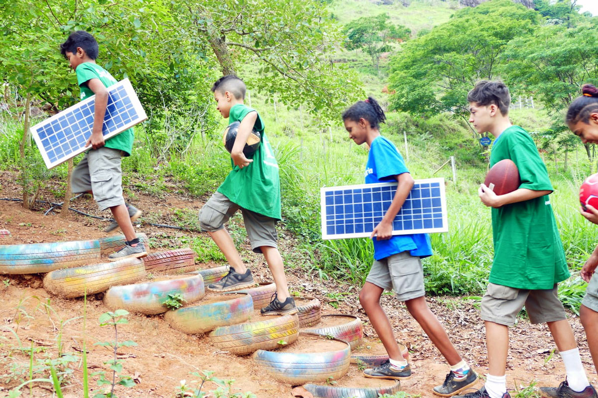 Five youth climb an outdoor staircase made with rainbow-colored tires. Two hold solar panels and three hold balls.