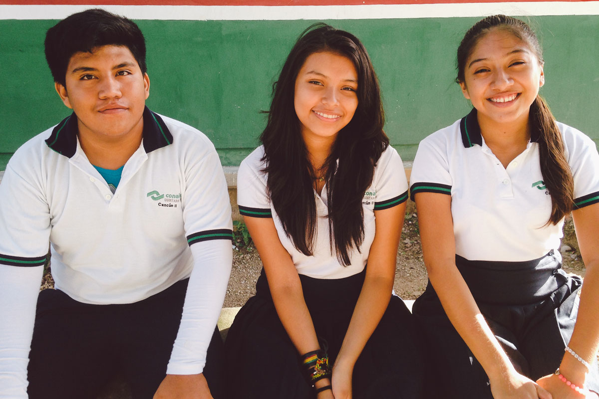Three adolescents in school uniforms sit on a bench outside against a green wall.