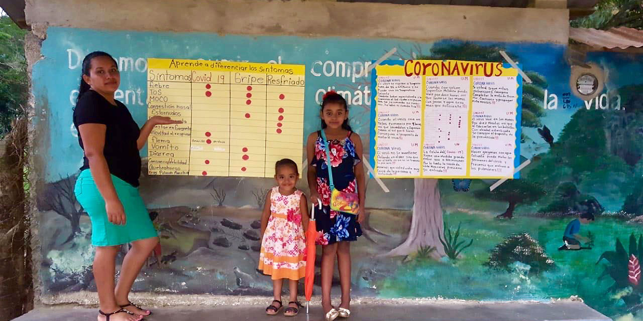 A woman and two children stand in front of posters with information about coronavirus.