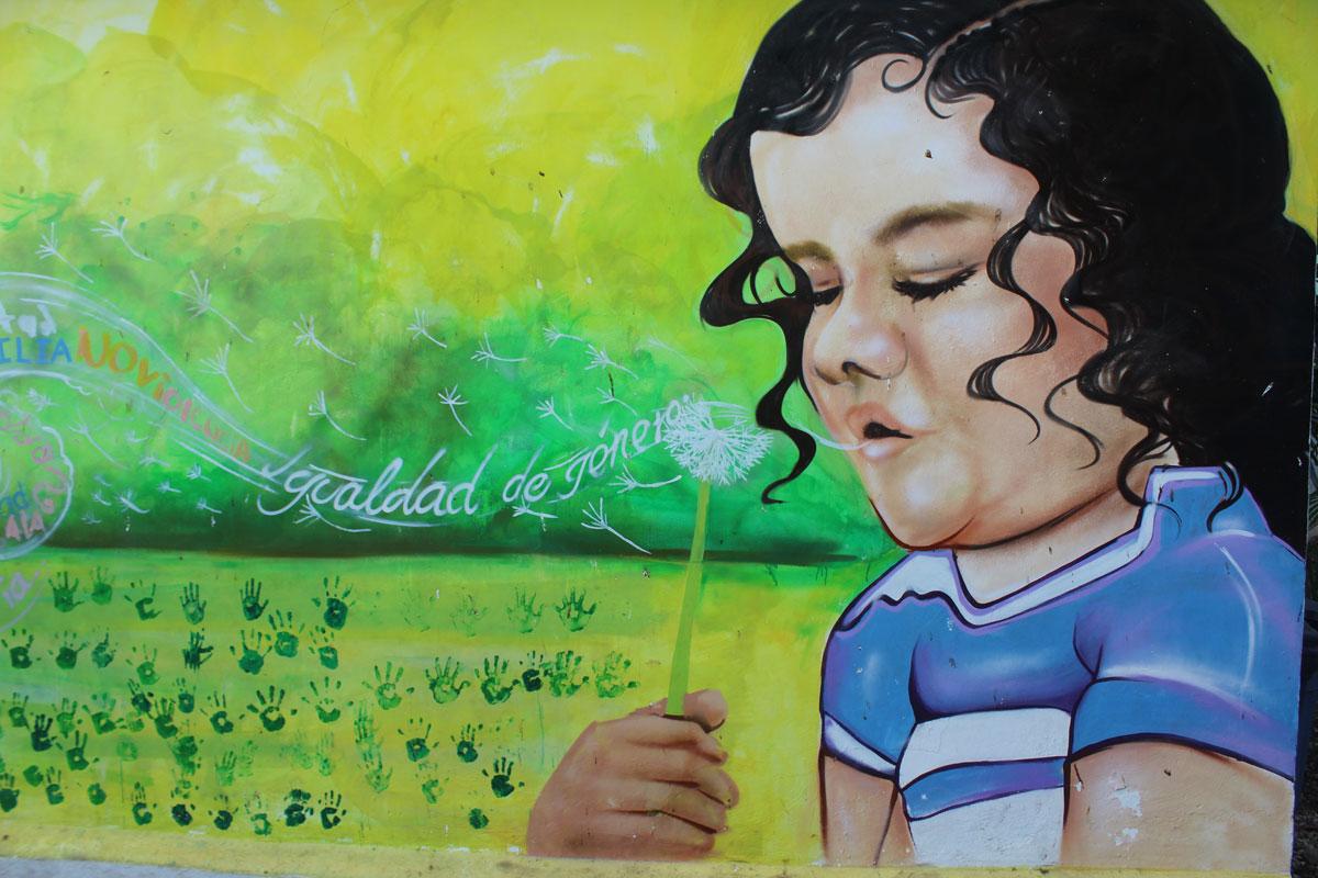 """A bright mural of a child blowing on a dandelion with the words """"No violencia. Igualdad de género."""""""
