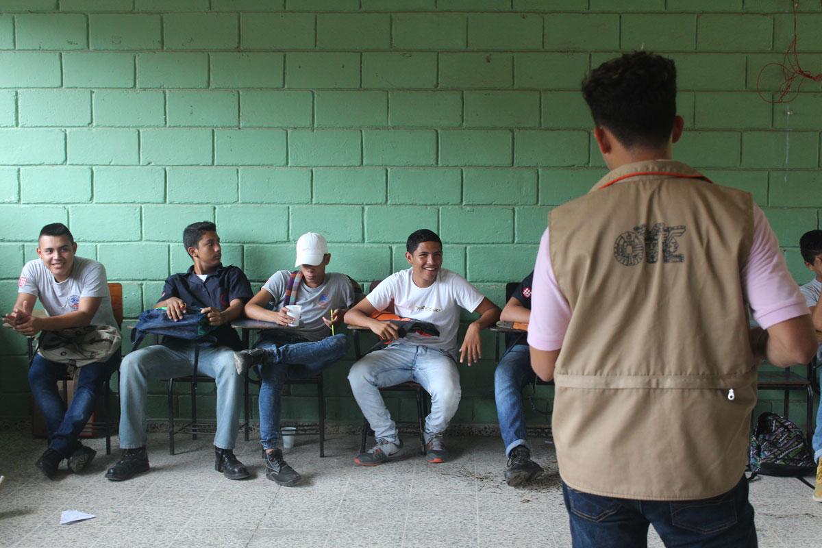 Young men sit at desks listening to a workshop facilitator.