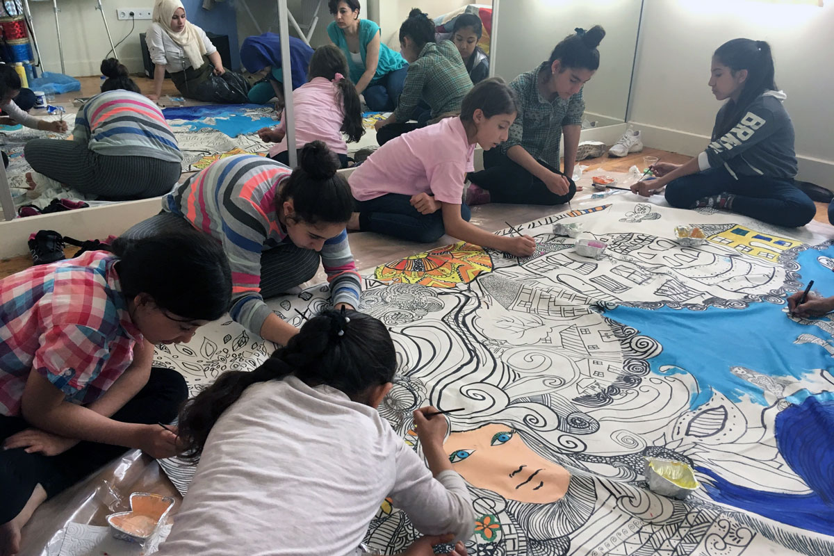 A group of girls sit on the floor around a large canvas, intently using colored paint to fill in a complex black-and-white outline with a woman's face, houses, and trees.
