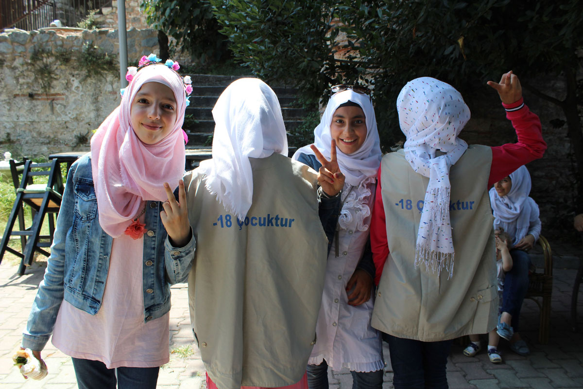 "Four girls pose for a photo, two facing the camera and two with their backs to the camera. They wear shirts that say ""-18Çocuktur."""