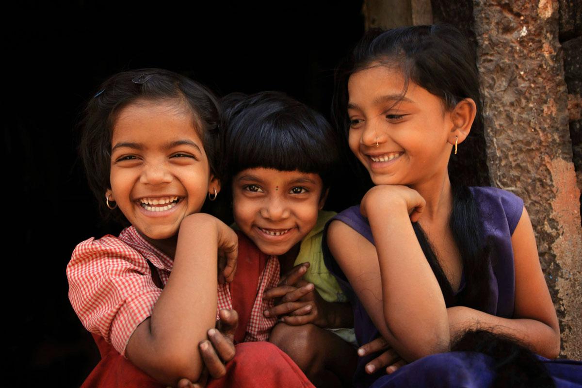 Three girls sit laughing.