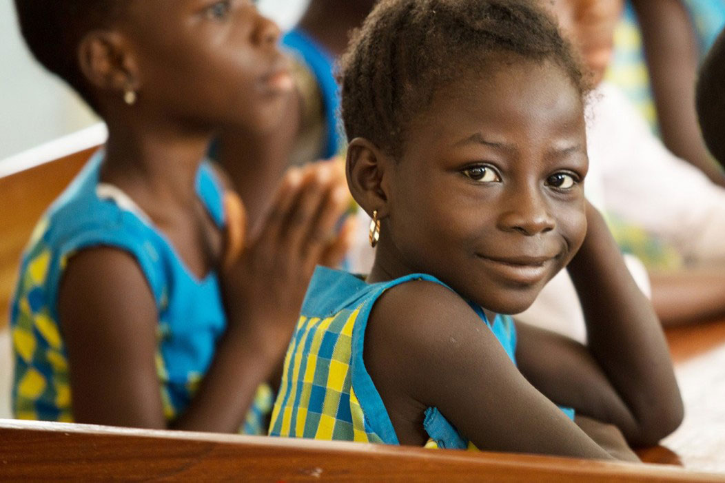 A girl in a classroom smiling.
