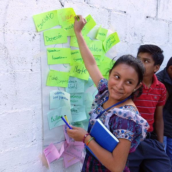 A girl turns her head as she writes a message on a white wall filled with green and blue sticky notes.