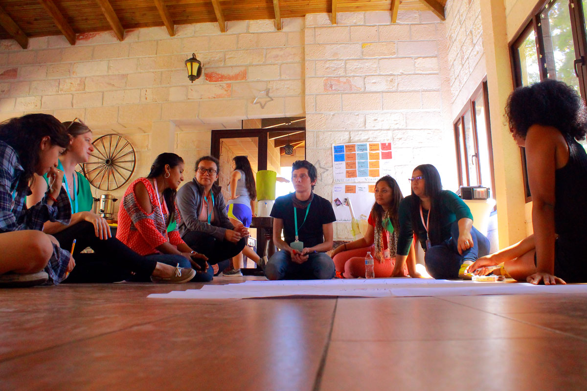 A group of five people have a discussion while sitting on a wooden floor, around a piece of flipchart paper.