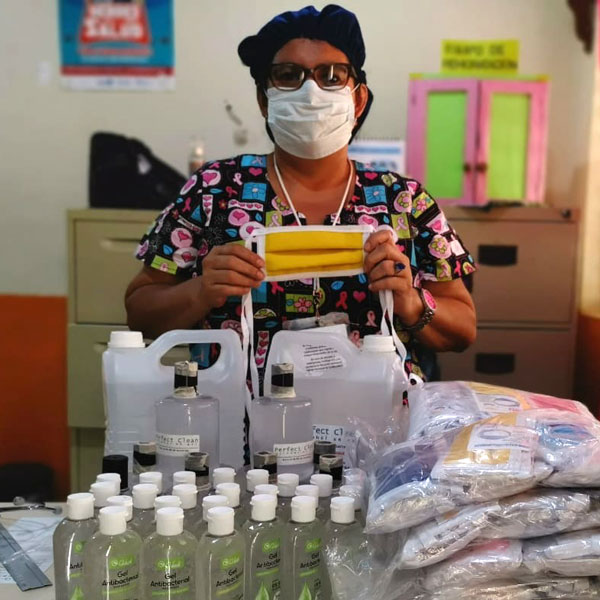 A woman wearing a medical face mask stands behind hand sanitizer and emergency supplies.