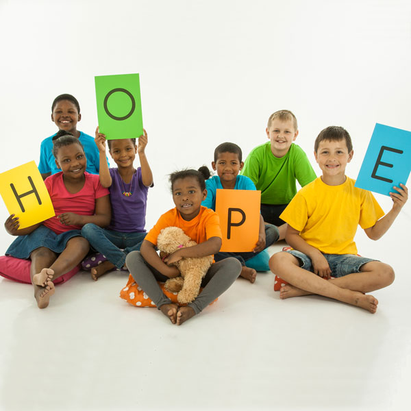 Seven children hold up colored paper with letters that spell the word HOPE.
