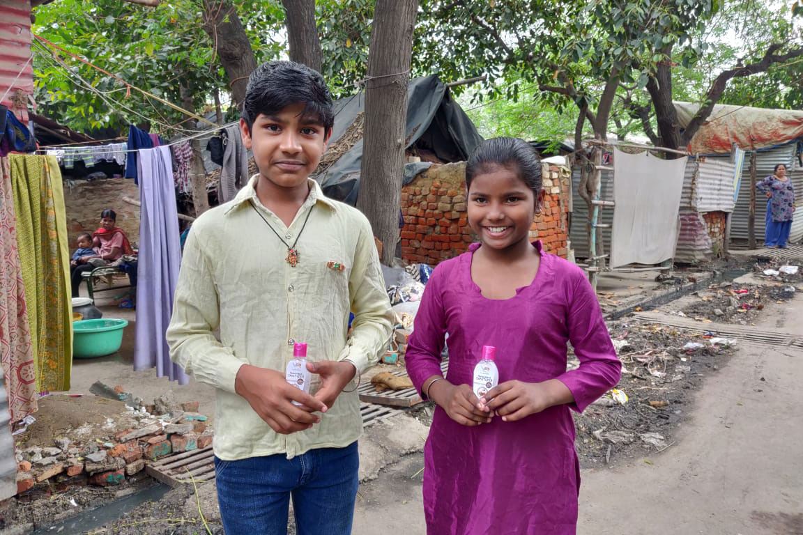 Two children in New Delhi hold bottles of hand sanitizer.