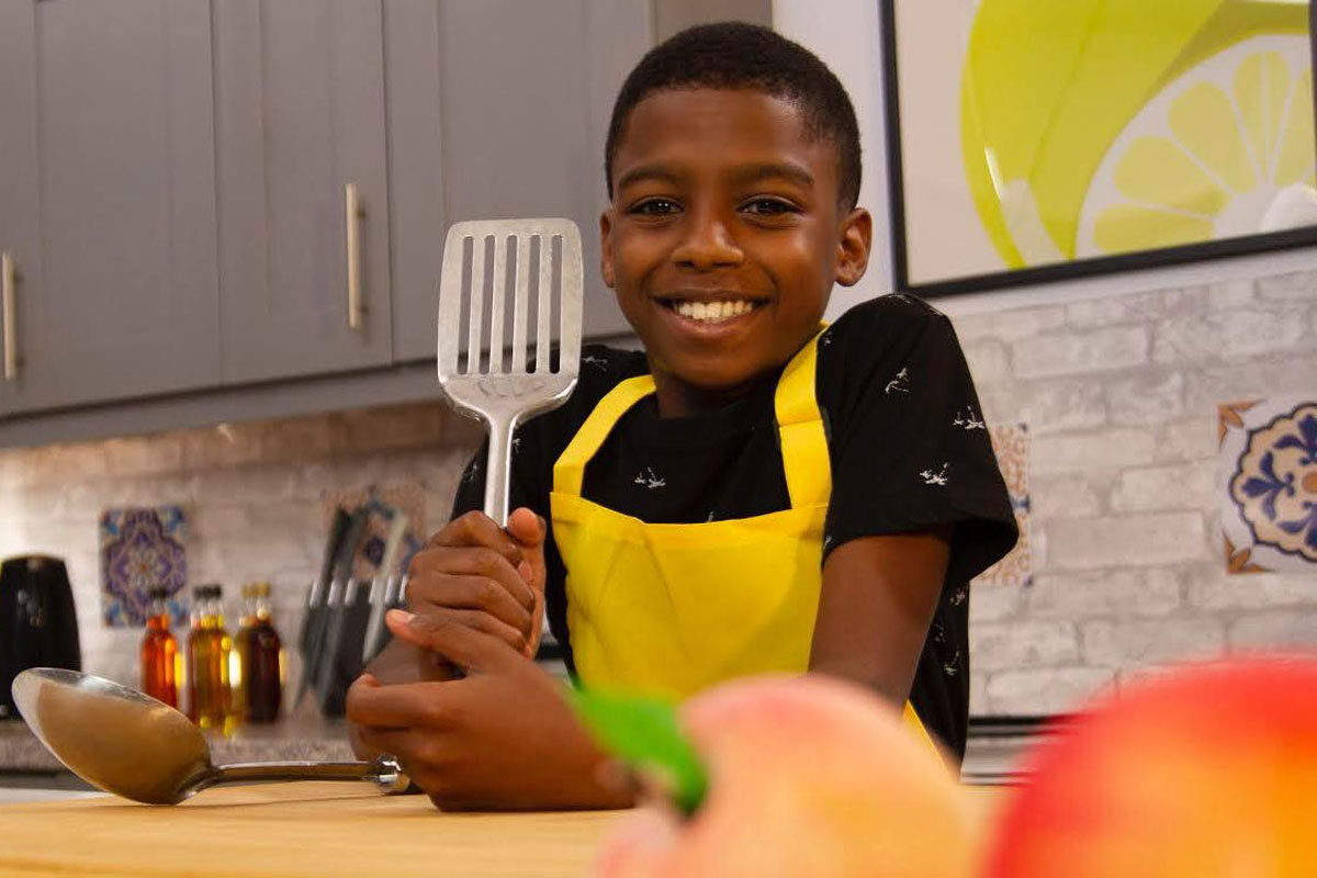 Omari McQueen stands in the kitchen holding a spatula.