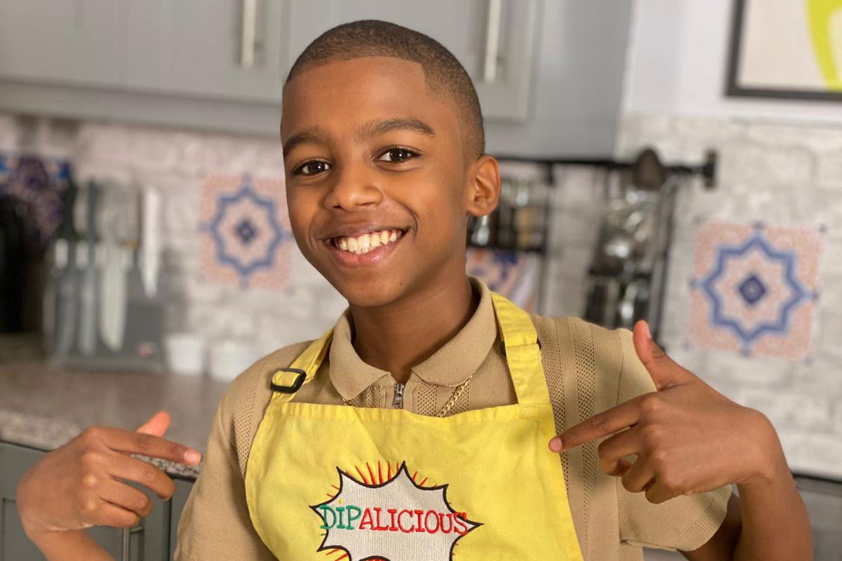 Omari McQueen points to his Dipalicious apron.