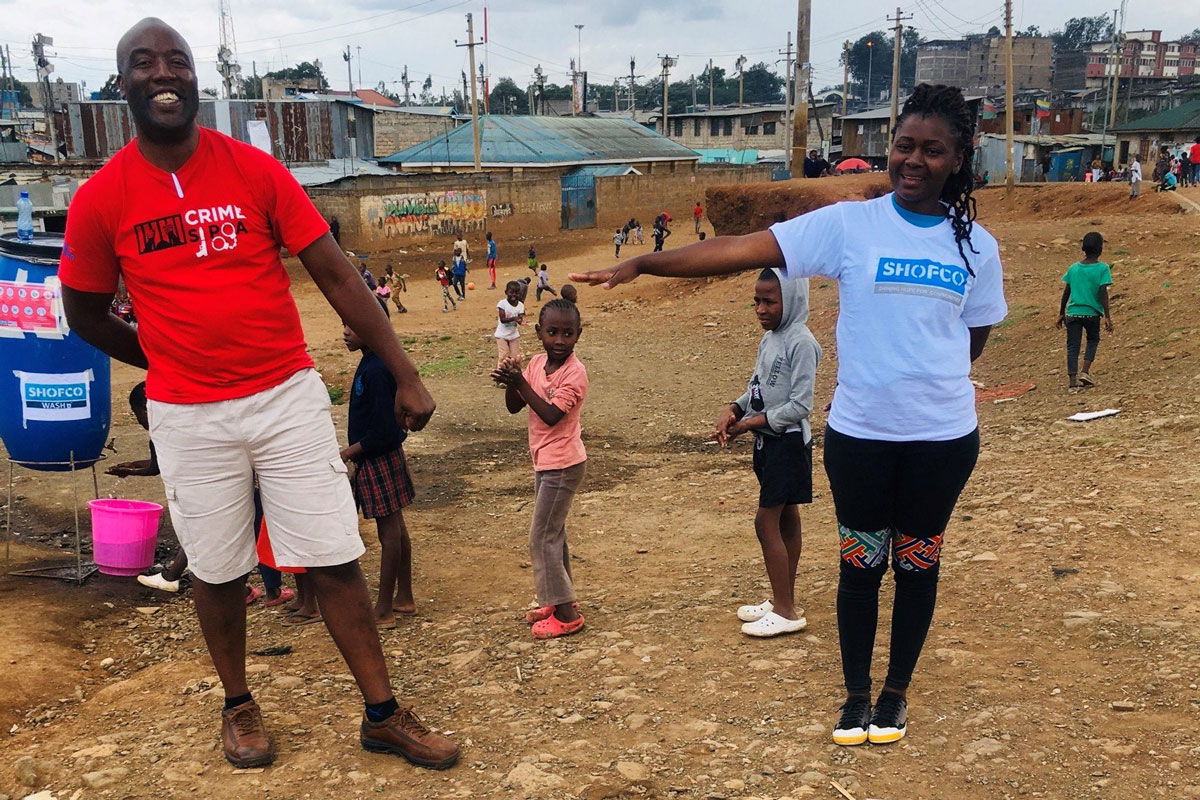 Peter Ouko from Youth Safety Awareness Initiative and Iryn Were from Shining Hope for Communities (SHOFCO) model social distancing for children in Nairobi's Mathare informal settlement.