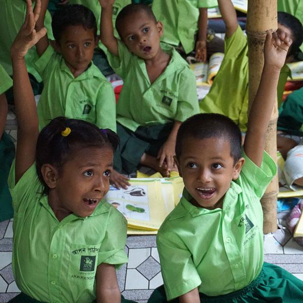 Children raise their hands during an APON Foundation program.