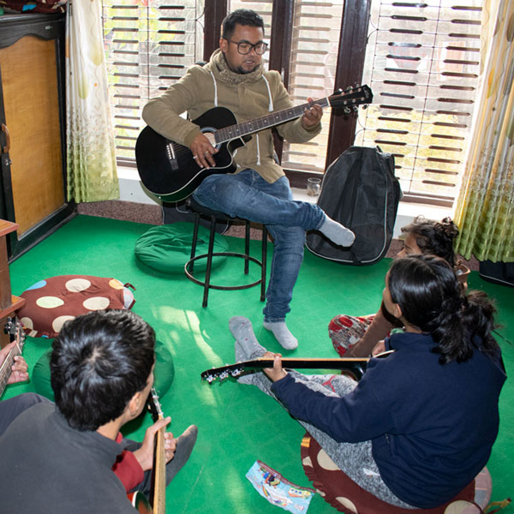 Children learning to play guitar as part of an Asha Nepal program.