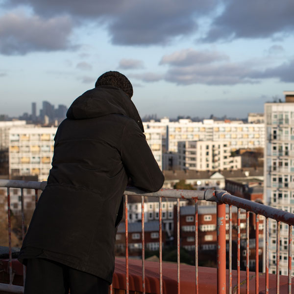 Cyrus on a balcony overlooking apartment buildings.