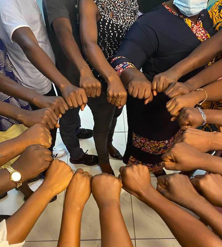 Meeting participants put their hands in a circle.