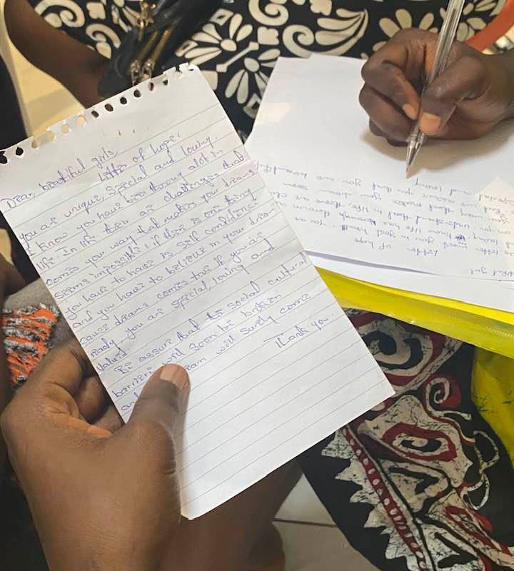 Participants in the meeting writing a letter to girls.