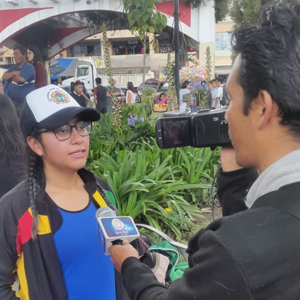 A young woman being interviewed by a reporter.