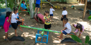 Children play on a seesaw in an outdoor playground. Photo credit: Kimlong Meng.