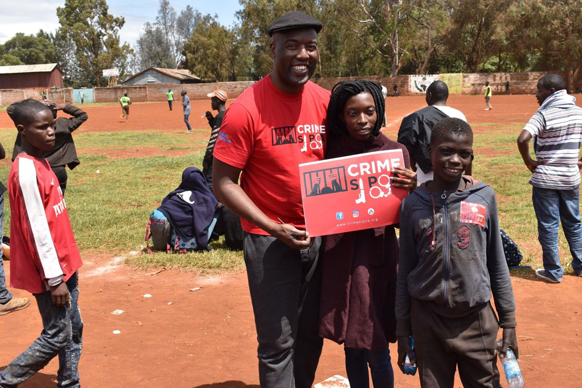 Peter Ouko poses for a picture with children participating in a Youth Safety Awareness Initiative program