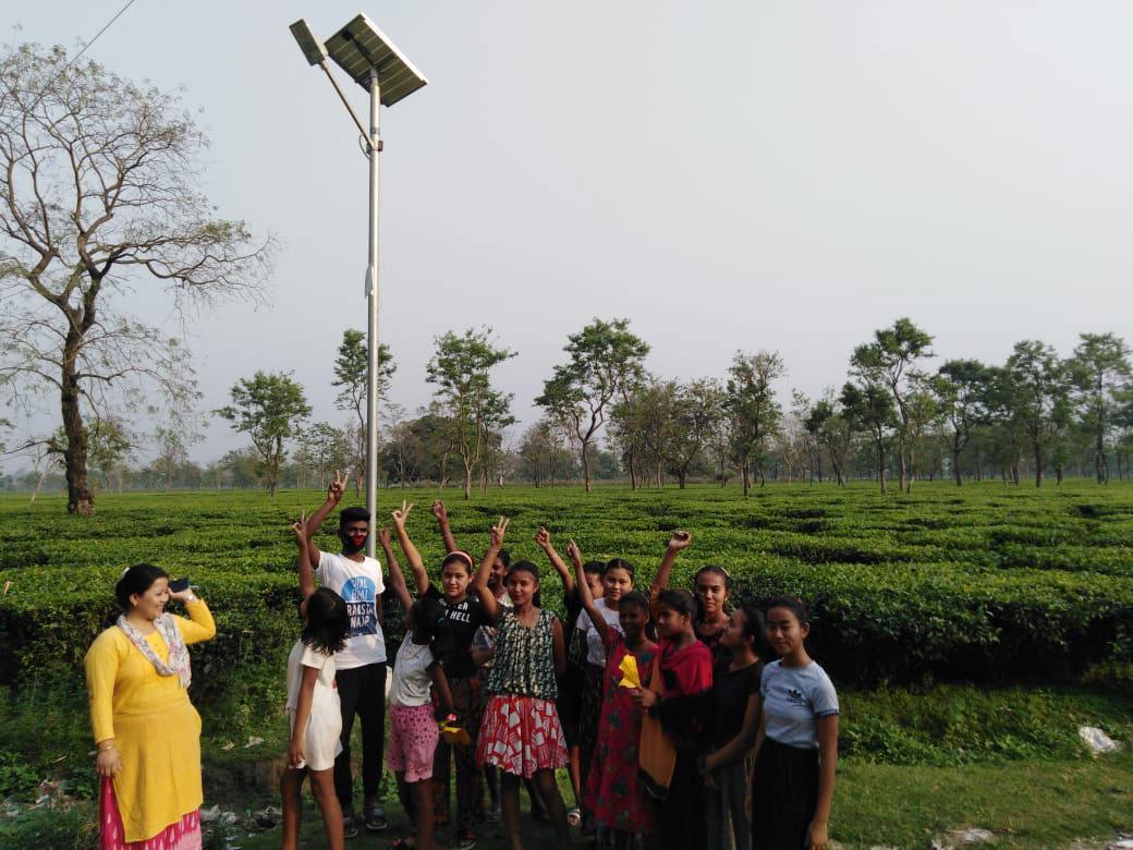 Children enjoying their achievement beneath a new solar streetlight